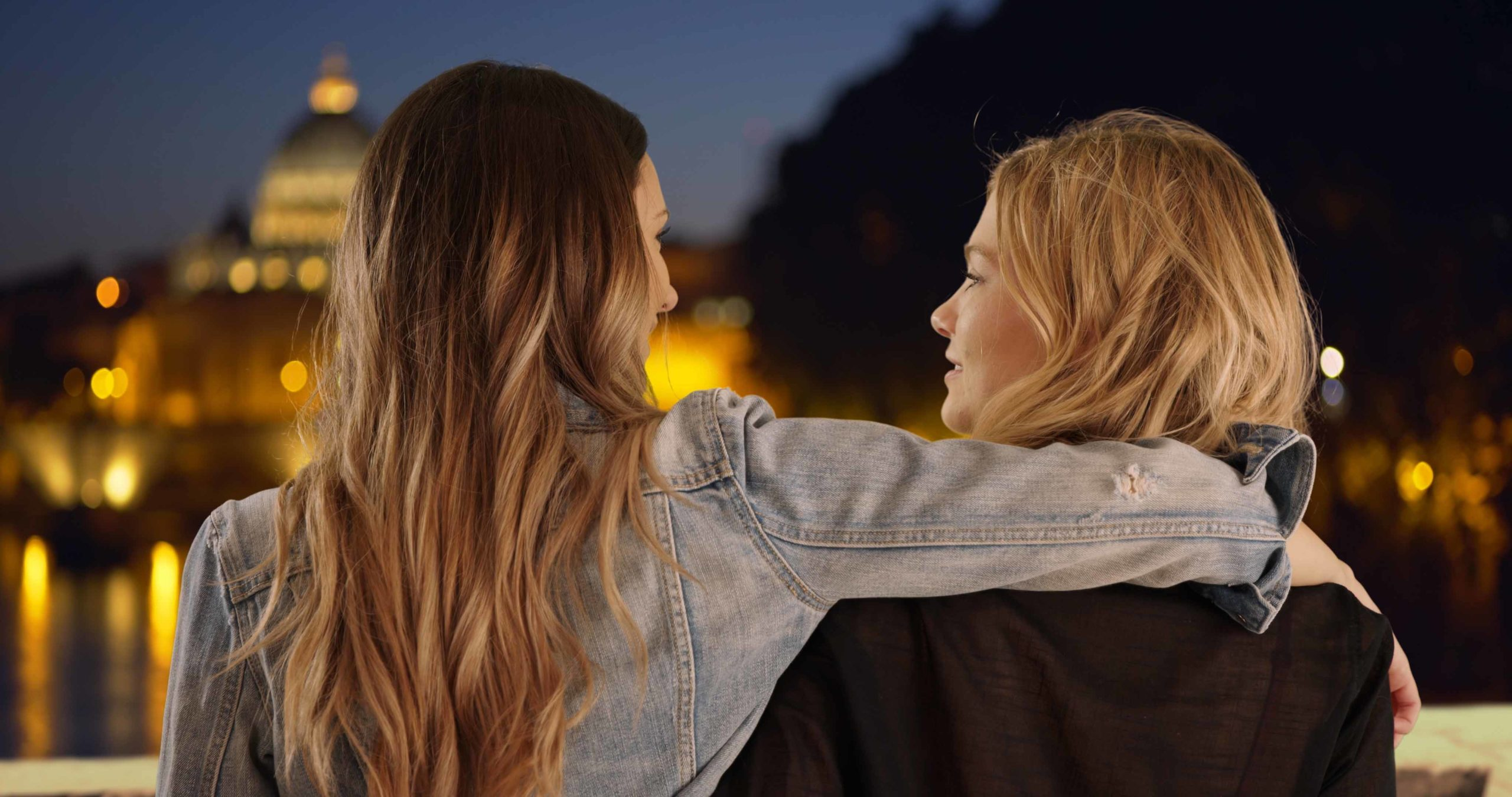 Young brunette with arm around blonde friend's shoulder in Rome Italy
